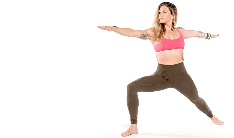 A woman strikes a standing yoga pose