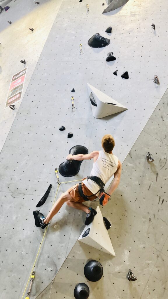 a man climbs a precarious rock formation on an indoor rock climbing wall