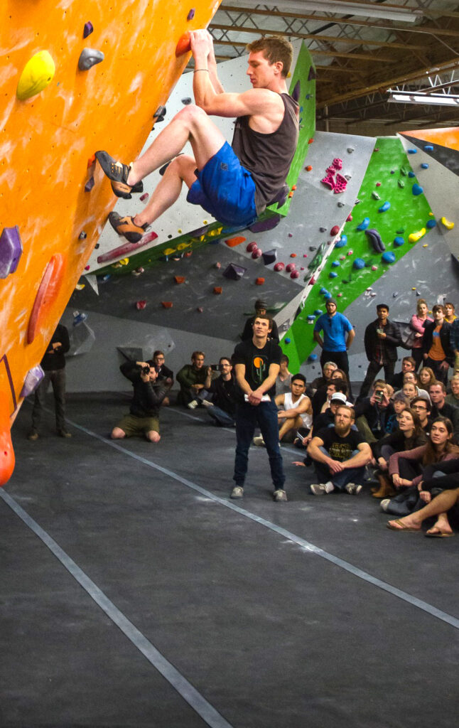 a person climbs an indoor rock wall while several people sit and watch with rapt attention