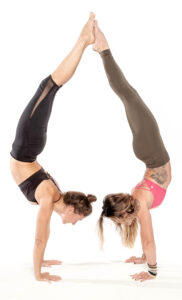 two women perform handstands back to back.