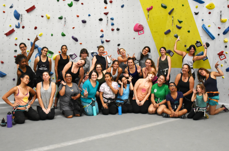 group of women in front of a climbing wall