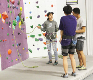 Woman teaching two young men how to tie into a rope for climbing.
