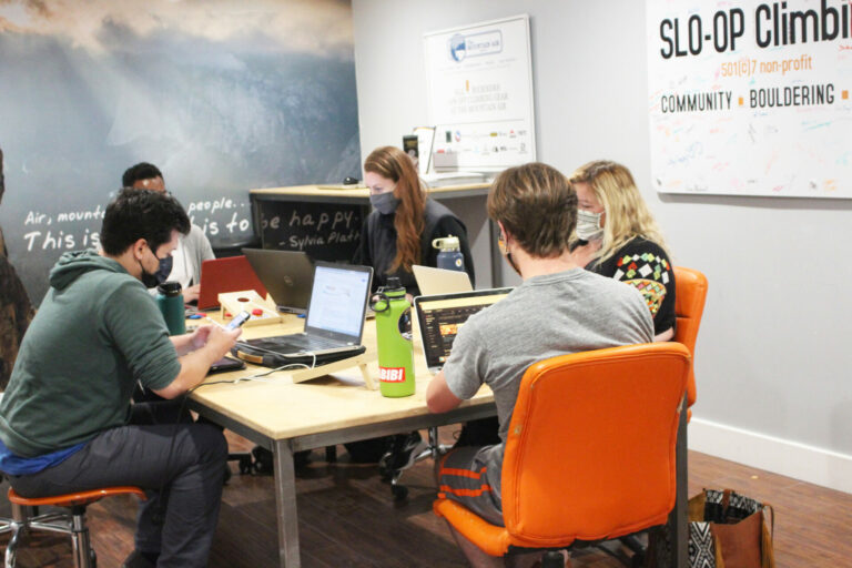 Group of people sitting at a desk in a lounge working.