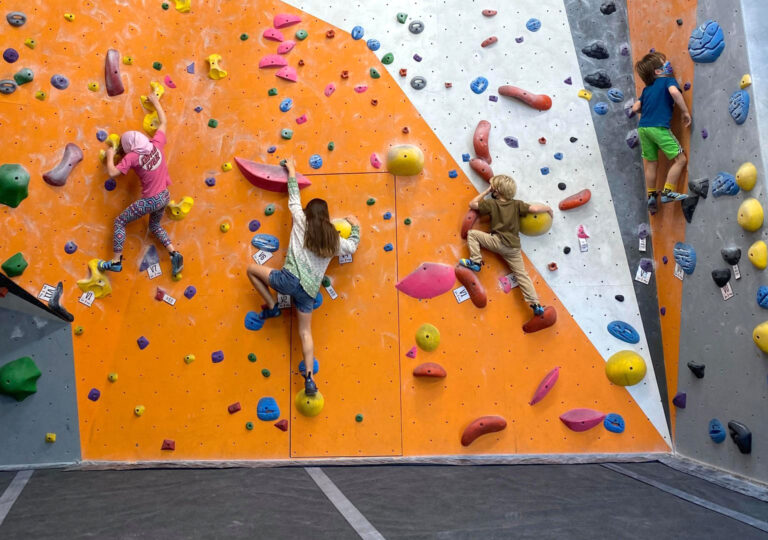 two people climb a white and orange indoor rock wall