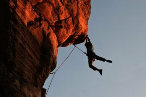Picture of a guy on an overhanging rope climb at sunset probably about to fall.