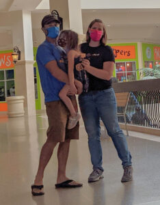 Family in a mall wearing masks