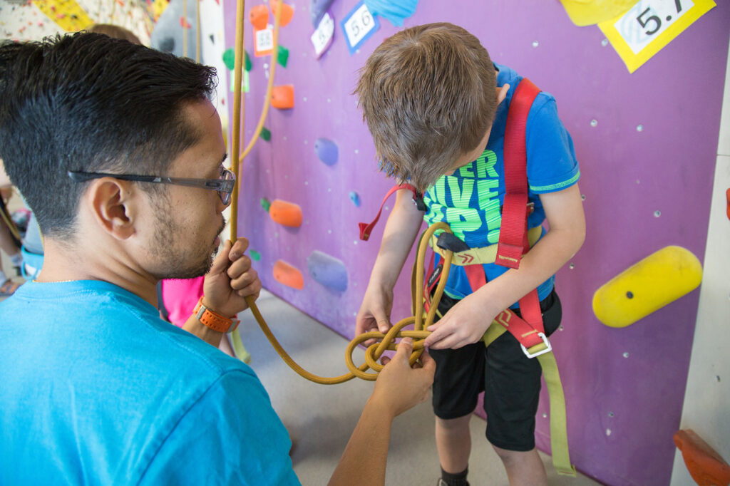 Man with glasses helps young boy put on harness for rock climbing in front of an indoor rock wall.