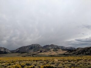 Mostly grey sky with dry high desert mountain landscape.