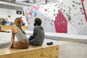 Woman in tank top and braid sits next to a man in a beard and a sweatshirt as they look at a climbing problem.