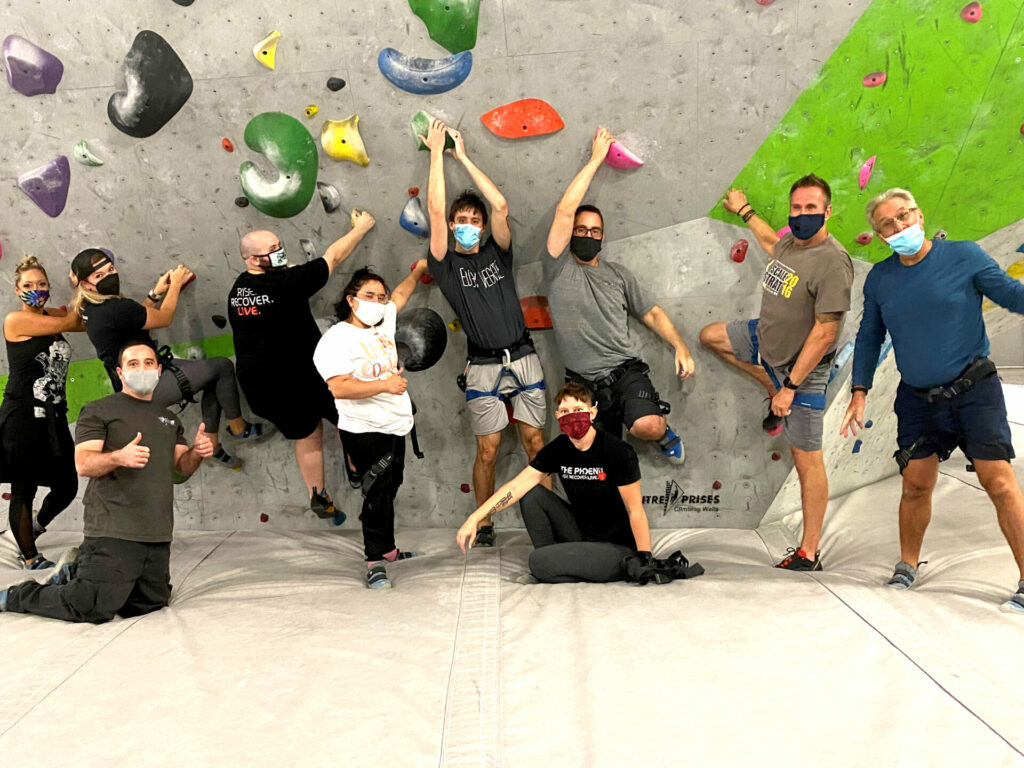 Group of people masked underneath a bouldering wall